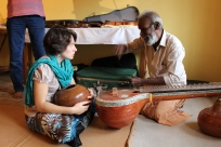 Nataraj demonstrates the finer point of veena making to Alex.