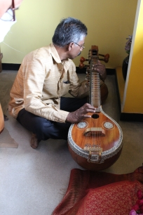 Murali, a carpenter from Kerala, tests the veena made by Nataraj